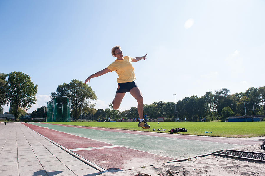 Senior Athlete (75) Practicing Long Jump Photograph by Lucy Lambriex