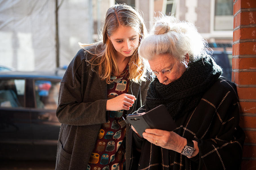 Senior Lady And Grandchild Looking At Smartphone Photograph by Lucy Lambriex