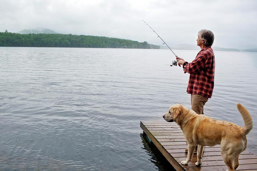 Animals Photograph - Senior Man Fishing Off Dock With Dog by Monica Donovan
