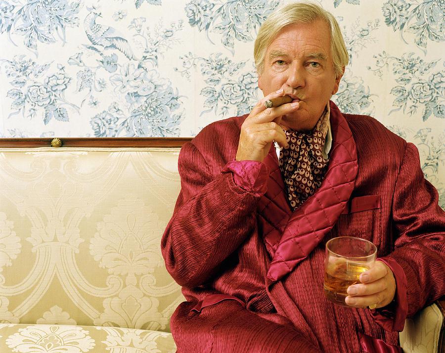 Senior man sitting on sofa, smoking cigar and holding glass, portrait Photograph by Digital Vision