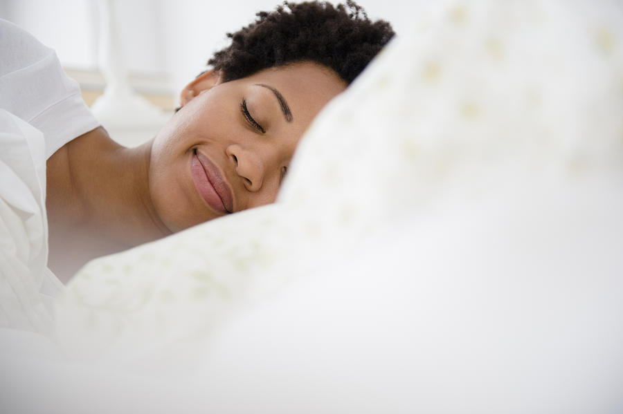 Serene Black woman laying in bed Photograph by JGI/Jamie Grill
