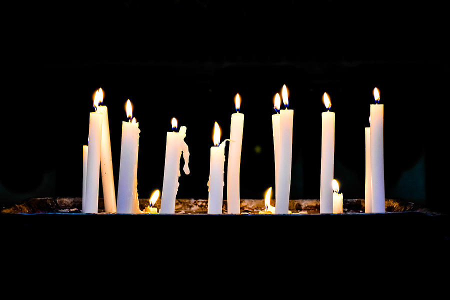 Several candlelights lit up against black background Photograph by Smartshots International
