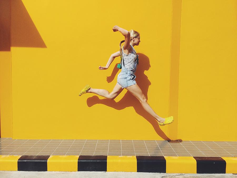 Side View Of Mid Adult Woman Jumping On Footpath Against Yellow Wall Photograph by Mikhail Novozilov / EyeEm