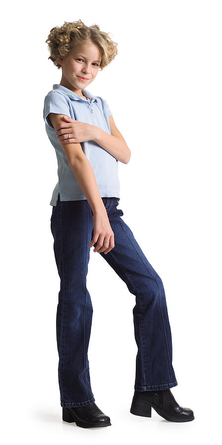 Silhouette Of A Caucasian Blonde Teenage Girl In Jeans And A Blue Shirt As She Turns And Smiles At The Camera Photograph by Photodisc