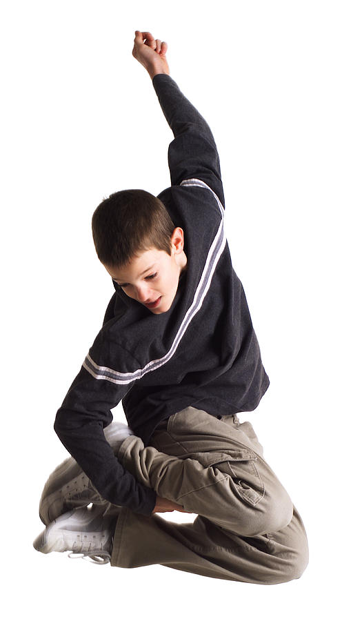 Silhouette Of A Caucasian Teenage Boy In Tan Pants And A Blue Shirt As He Jumps Up And Grabs His Feet Photograph by Photodisc