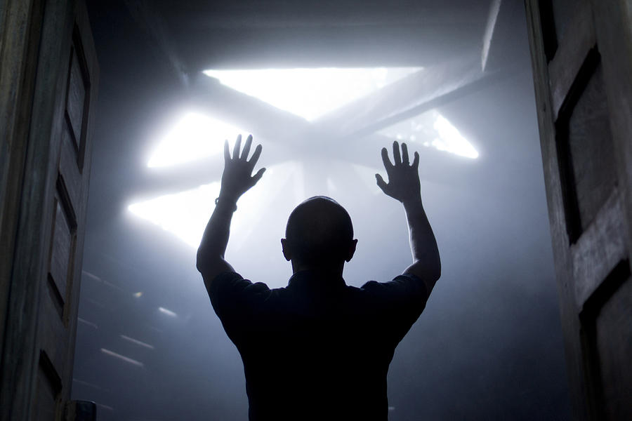 Silhouette Of A Man With Raised Hands Against Light Coming From Above. Photograph by Maciej Toporowicz, NYC