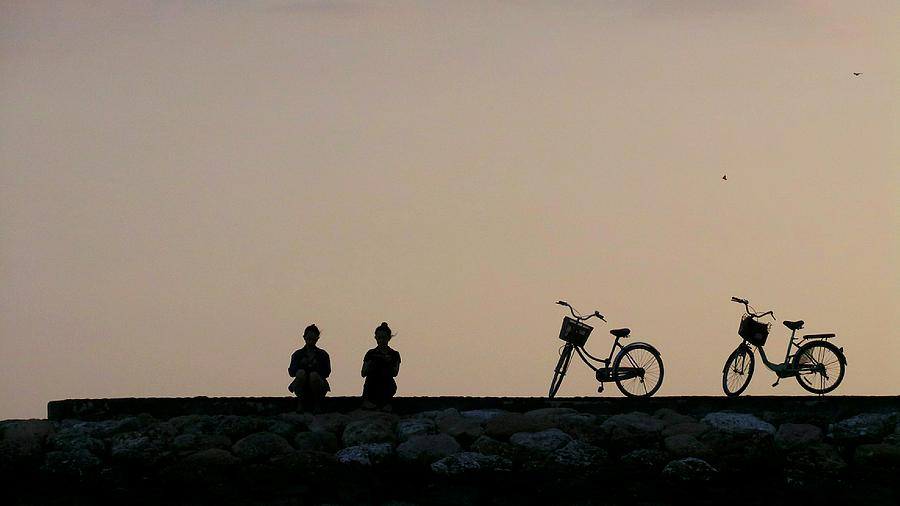 Silhouette People Sitting On Retaining Wall Against Sky During Sunset Photograph by Joseph Jeanmart / EyeEm