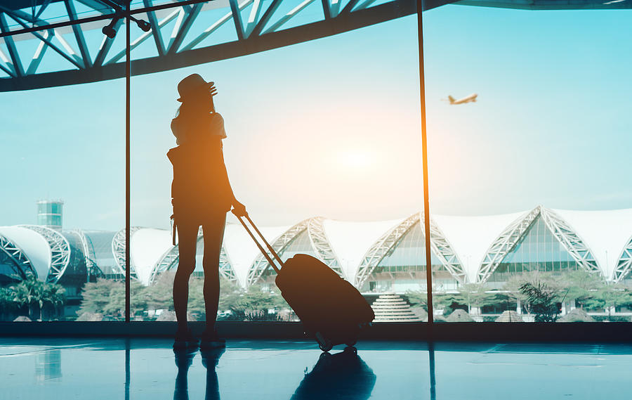 Silhouette Woman With Luggage Standing In Airport Photograph by Kiattisak Lamchan / EyeEm