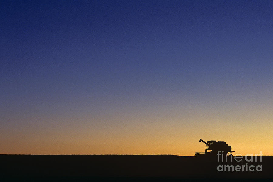 Agriculture Photograph - Silhouetted combine in field at sunrise by Jim Corwin