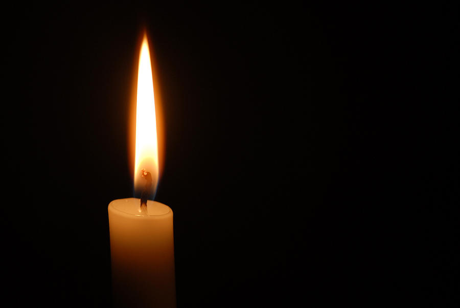 Single candle flame on horizontal black background Photograph by Lighthousebay