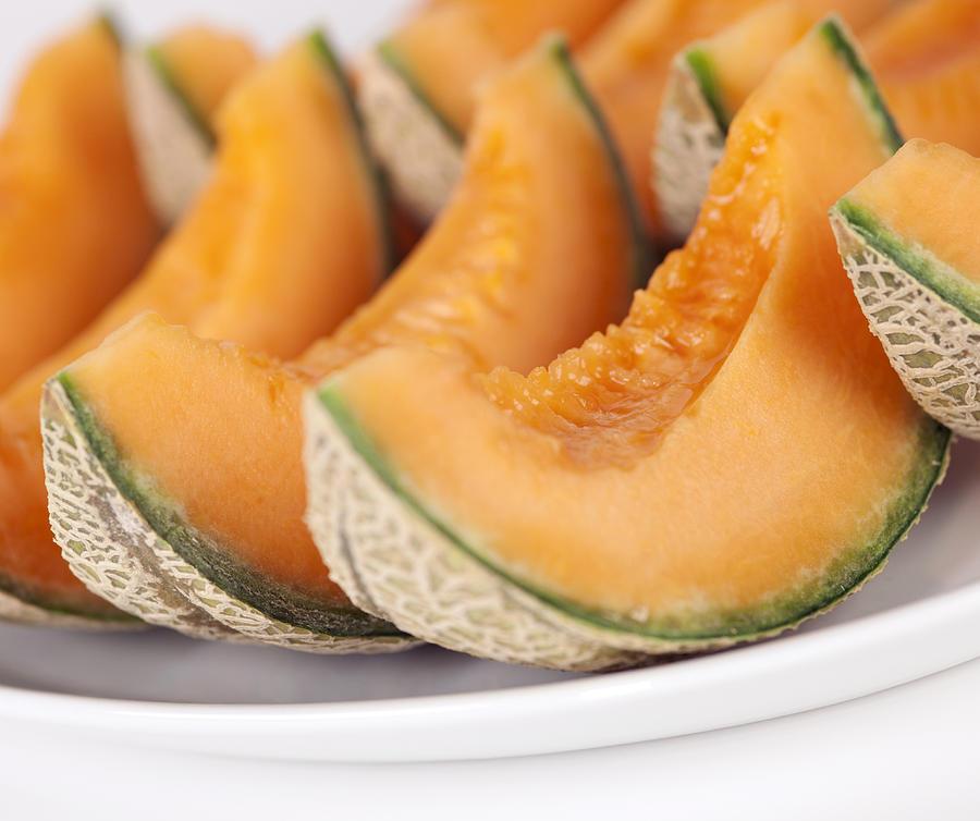 Sliced cantaloupe melons on a plate Photograph by Josef Mohyla