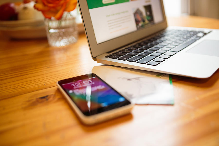 Smartphone and laptop on kitchen table Photograph by Heshphoto