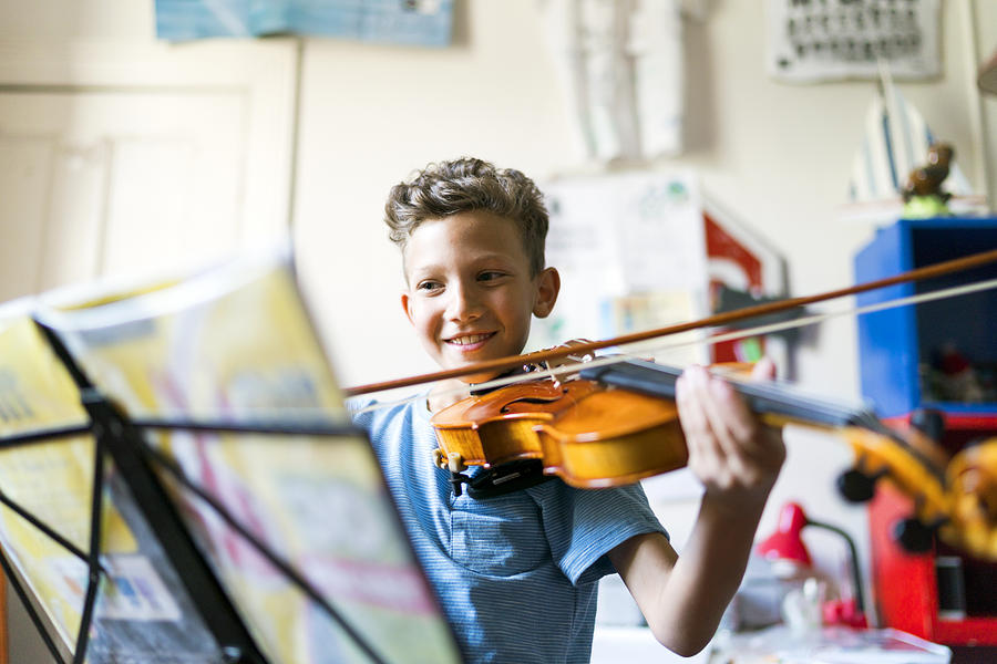 Smiling boy playing violin in domestic room Photograph by Portra