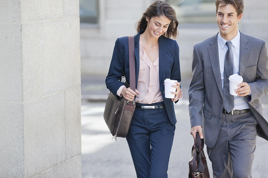 Smiling businessman and businesswoman walking with coffee cups Photograph by Sam Edwards