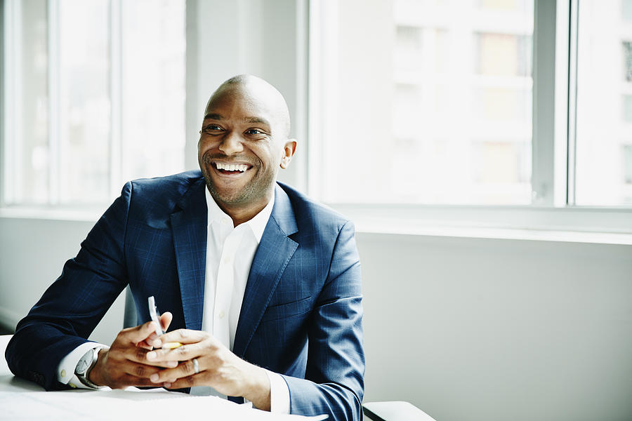 Smiling businessman in discussion at workstation Photograph by Thomas Barwick