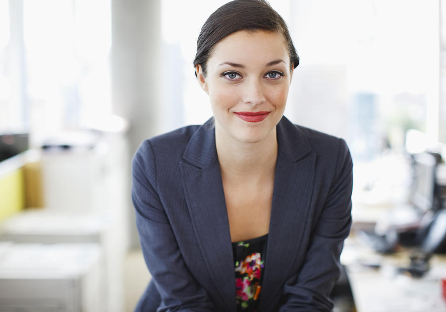Smiling businesswoman in office Photograph by Daly and Newton