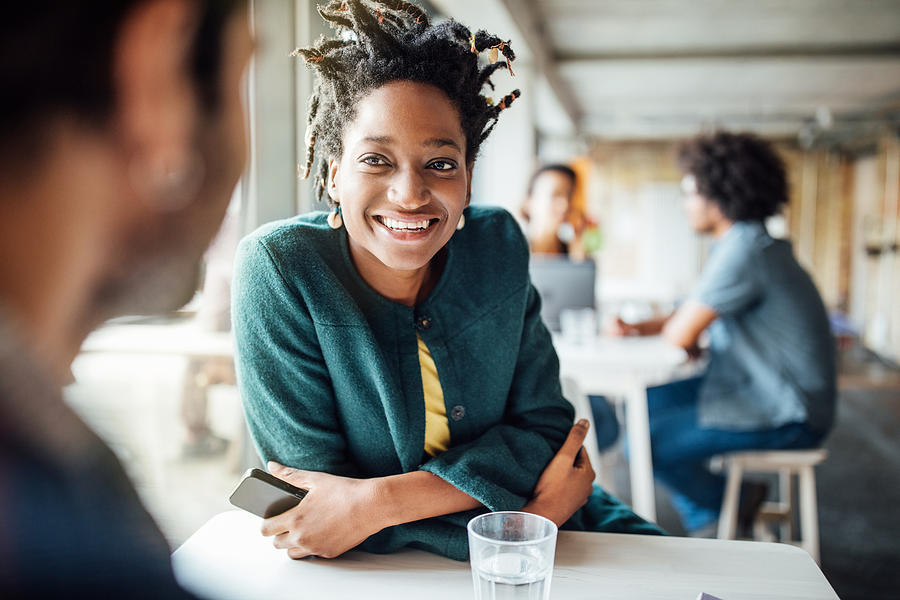 Smiling Businesswoman Sitting With Colleague In Cafeteria Photograph by Luis Alvarez