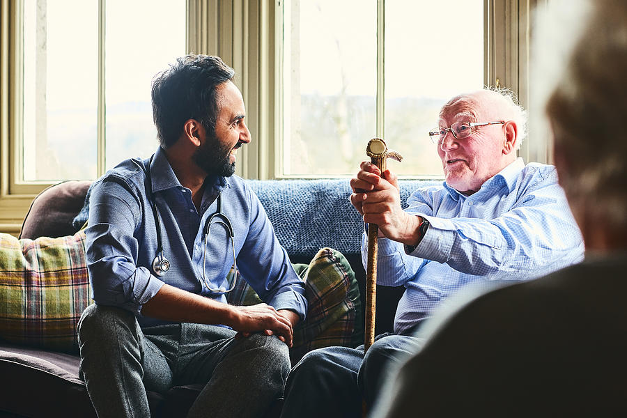 Smiling doctor visiting senior man at home Photograph by Dean Mitchell