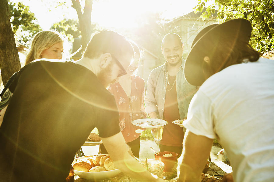 Smiling friends dishing up food in backyard on summer evening Photograph by Thomas Barwick
