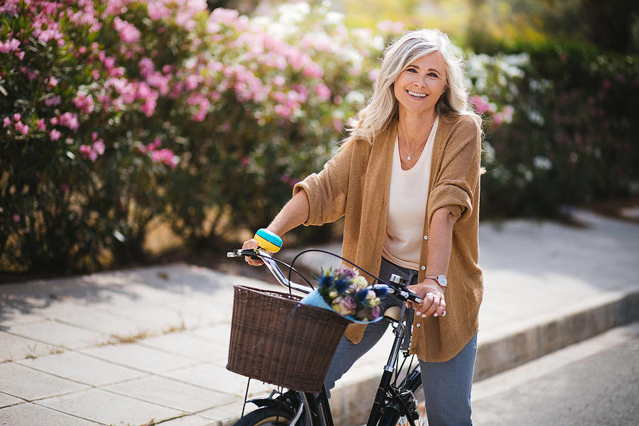 Smiling senior woman having fun riding vintage bike in spring Photograph by Wundervisuals