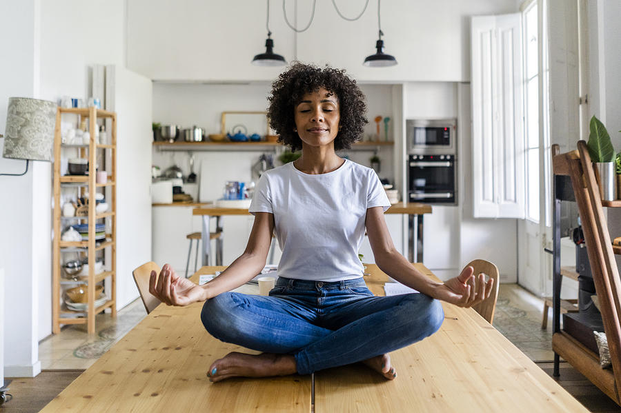 Smiling woman with closed eyes in yoga pose on table at home Photograph by Westend61