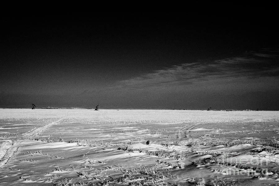 Oil Photograph - snow covered prairie agricultural farming land with pumpjacks oilfield winter Forget Saskatchewan Ca by Joe Fox