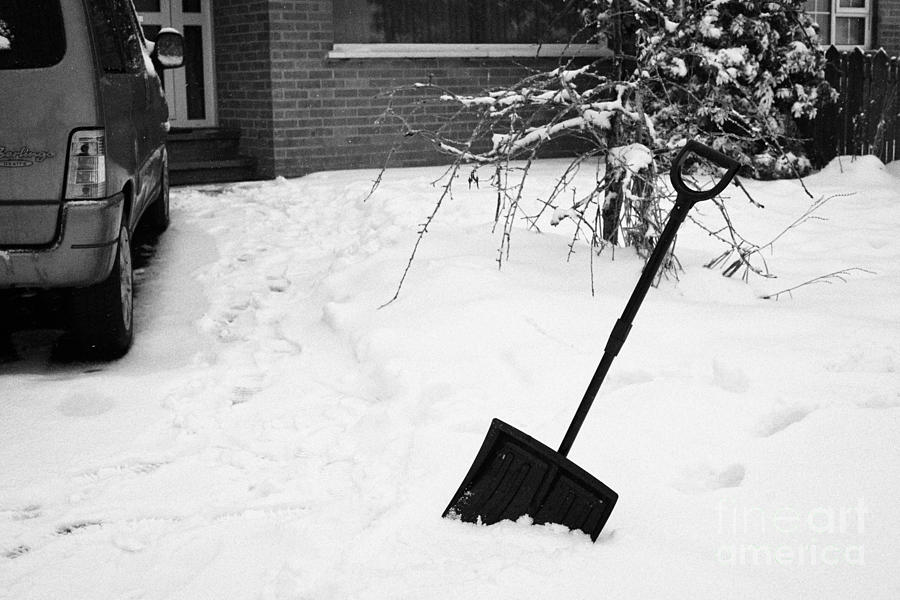 Snow Scoop Shovel In Deep Snow Clearing Driveway During Bad Winter Weather Newtownabbey Uk Photograph by Joe Fox