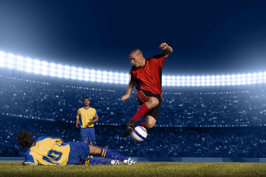 Soccer Player Jumping With Ball Photograph by Kycstudio