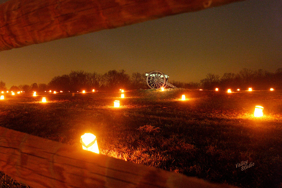 Looking Through A Split-rail Fence At A Solitary Cannon That Sits In The Middle Of This Field And Is Surrounded By Hundreds Of Luminaries. Each Year 23 Photograph - Solitary Cannon 12 by Judi Quelland