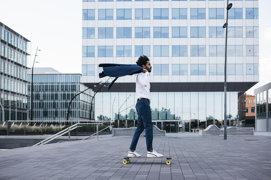 Spain, Barcelona, young businessman riding skateboard in the city Photograph by Westend61