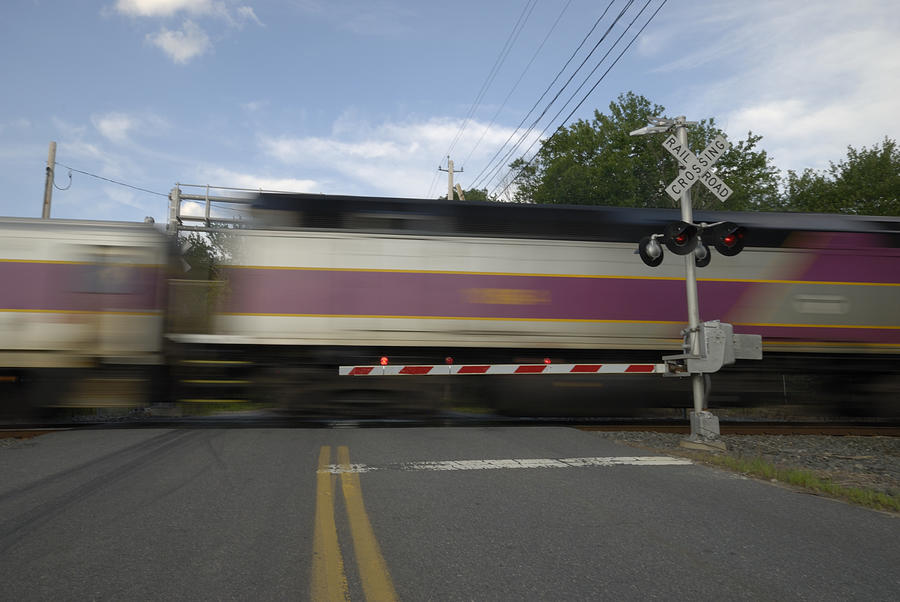 Speeding train crossing a street Photograph by JimDPhoto