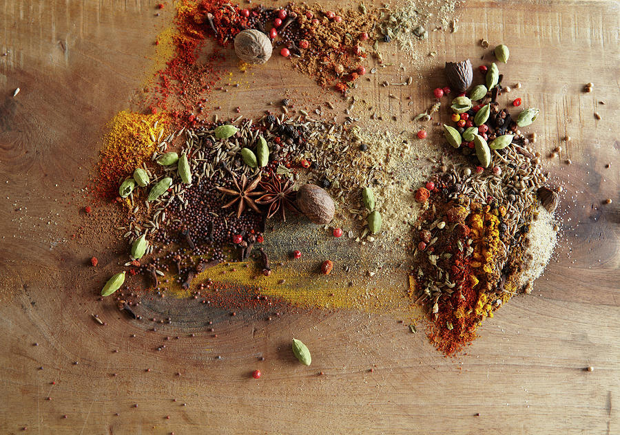 Spices Piled On Wood Surface Photograph by Maren Caruso