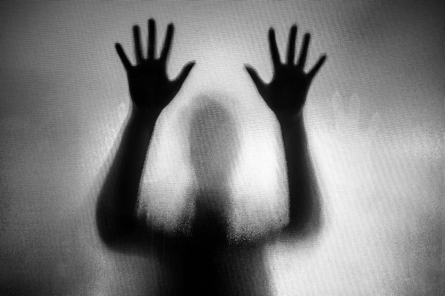 Spooky silhouette of woman with hands pressed against glass window Photograph by Coldsnowstorm