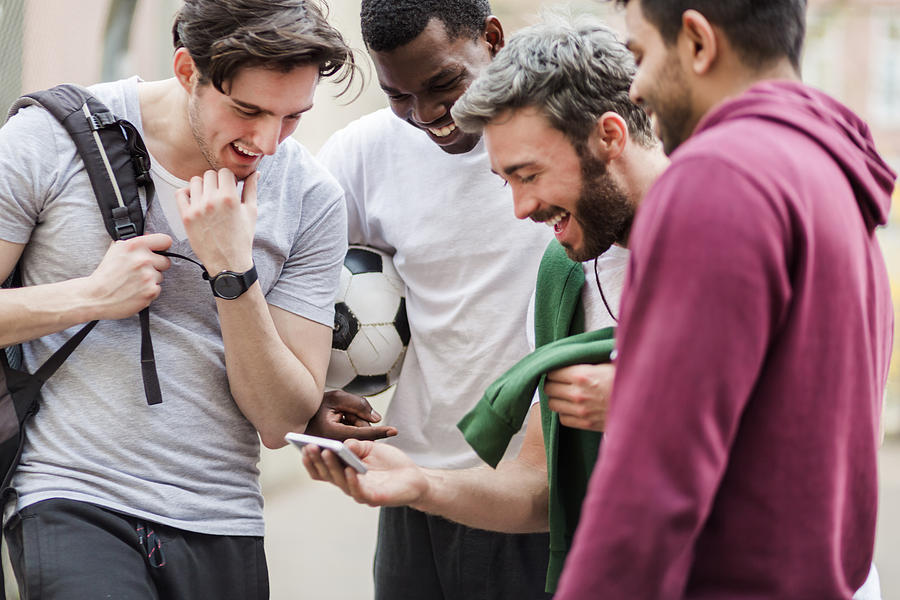 Sports Guys With Smart Phone Having Fun Photograph by Hinterhaus Productions
