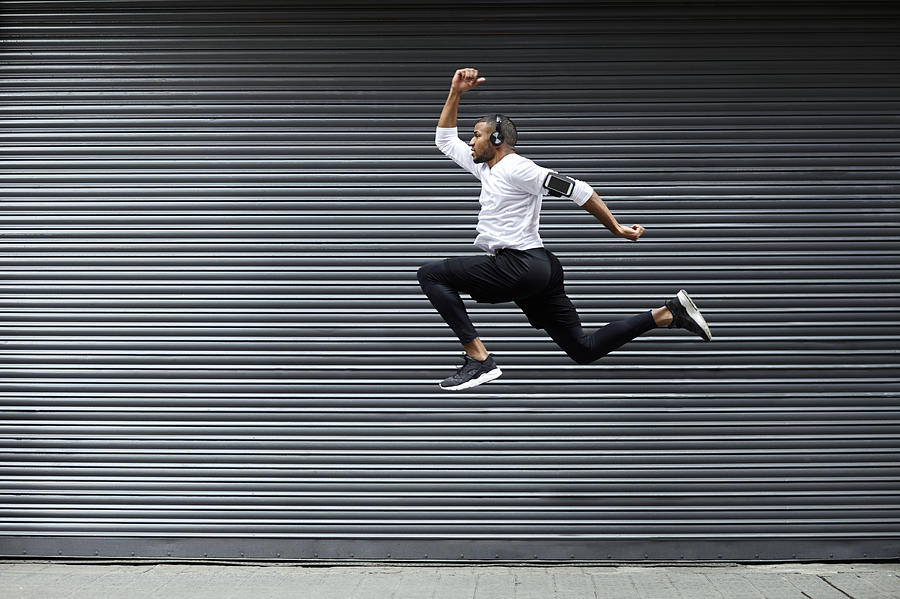 Sporty young man jumping against shutter Photograph by Morsa Images