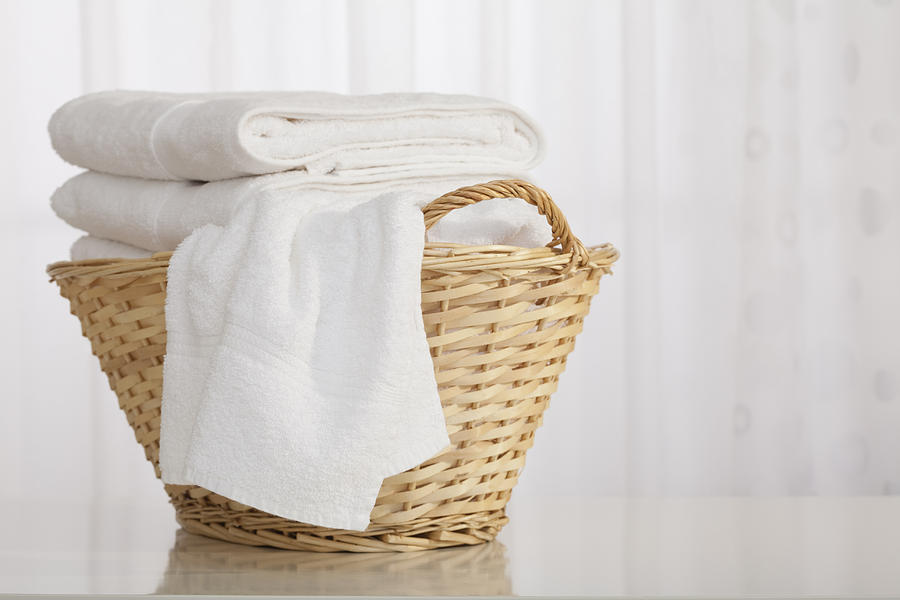 Studio shot of stack of white towels in Wicker Basket Photograph by Vstock LLC
