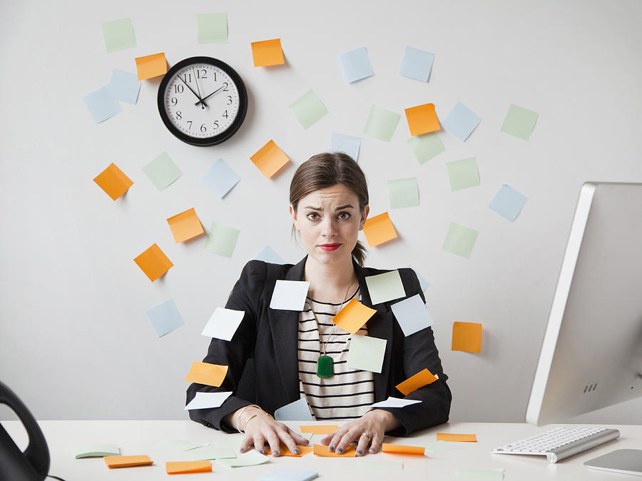 Studio shot of young woman working in office covered with adhesive notes Photograph by Jessica Peterson
