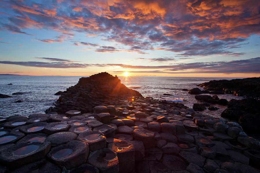 Water's Edge Photograph - Sunset Over The Giants Causeway by Gareth Mccormack