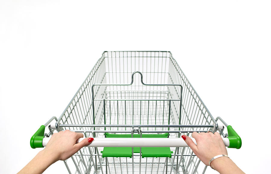 Supermarket trolley with womans hands on white Photograph by Peter Dazeley