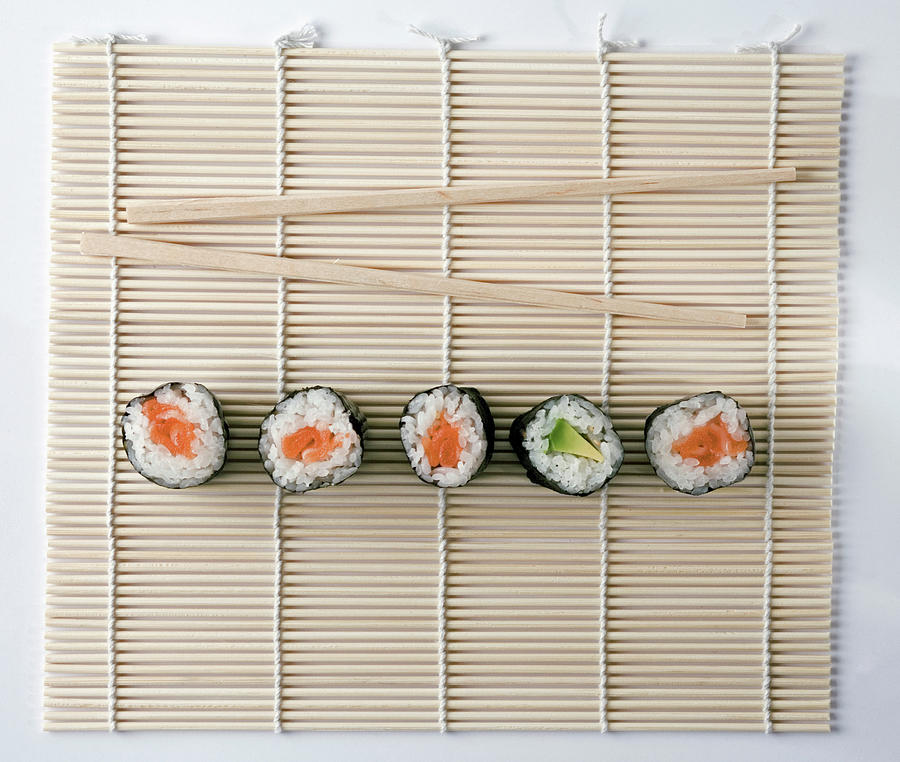 Sushi And Chopsticks On A Wooden Mat Photograph by Larry Washburn