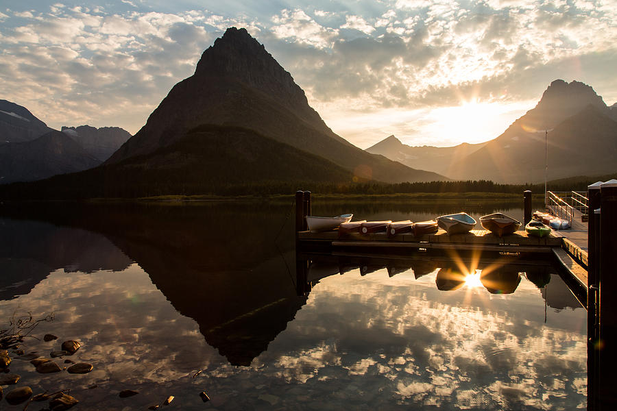 Reflection Photograph - Swiftcurrent Lake Boats Reflection And Flare by John Daly