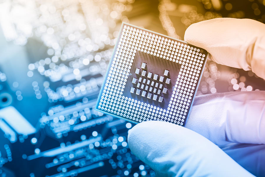 Technician holding chip over defocused circuit board Photograph by Krystiannawrocki