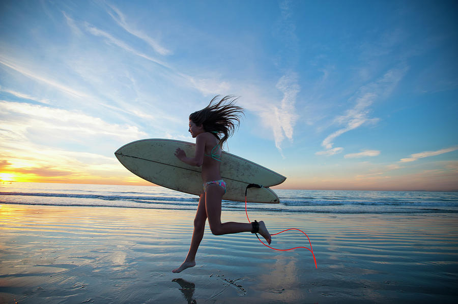 Teen Girl Running Leaping To The Surf Photograph by Stephen Simpson