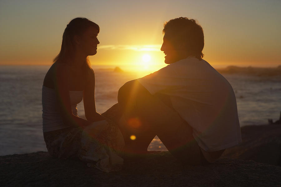 Teenage couple (15-19) sitting face to face on beach, sunset Photograph by Plustwentyseven