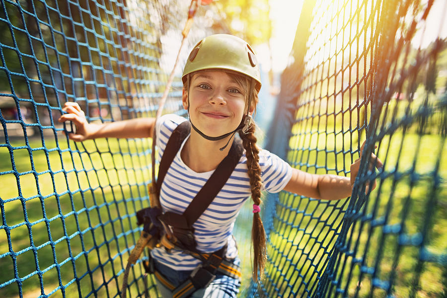 Teenage girl having fun in ropes course adventure park Photograph by Imgorthand