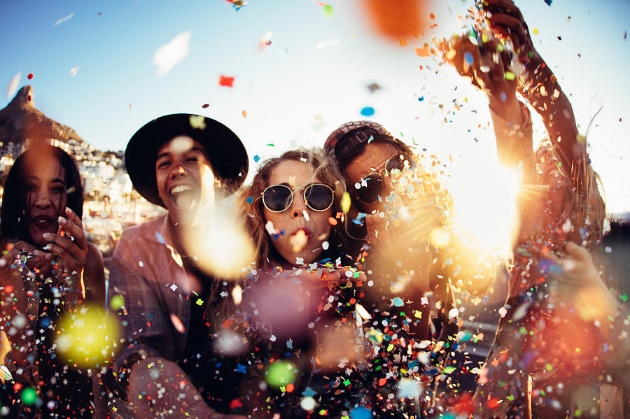 Teenager hipster friends partying by blowing colorful confetti from hands Photograph by Wundervisuals