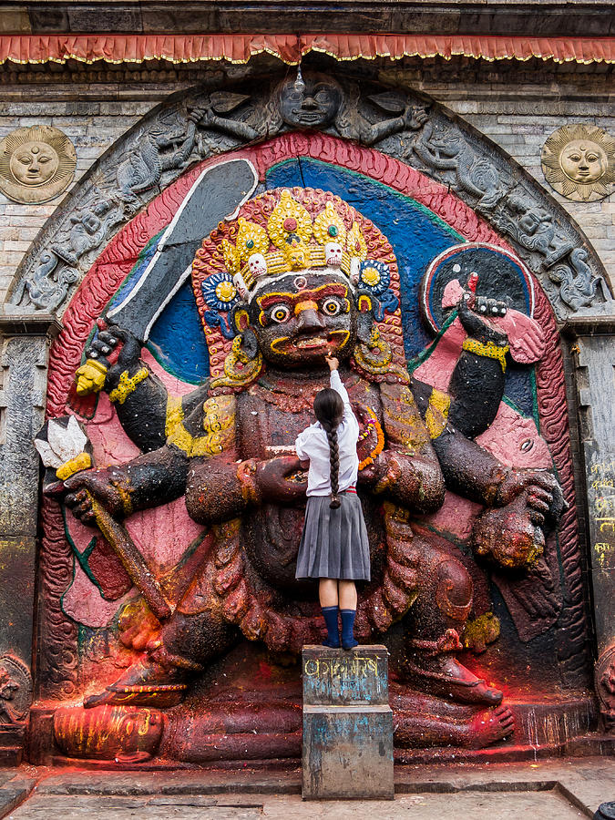 A Nepali School Girl Offers a Butter Lamp to the Fearsome Kala Bhairava by Nila Newsom