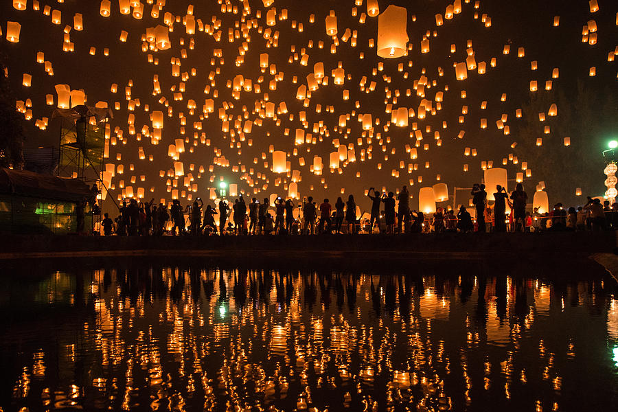 Thousands of Lanterns in the sky with the reflection on the water with people watching.Yeepeng festival, Chiangmai, Thailand Photograph by ImpossiAble