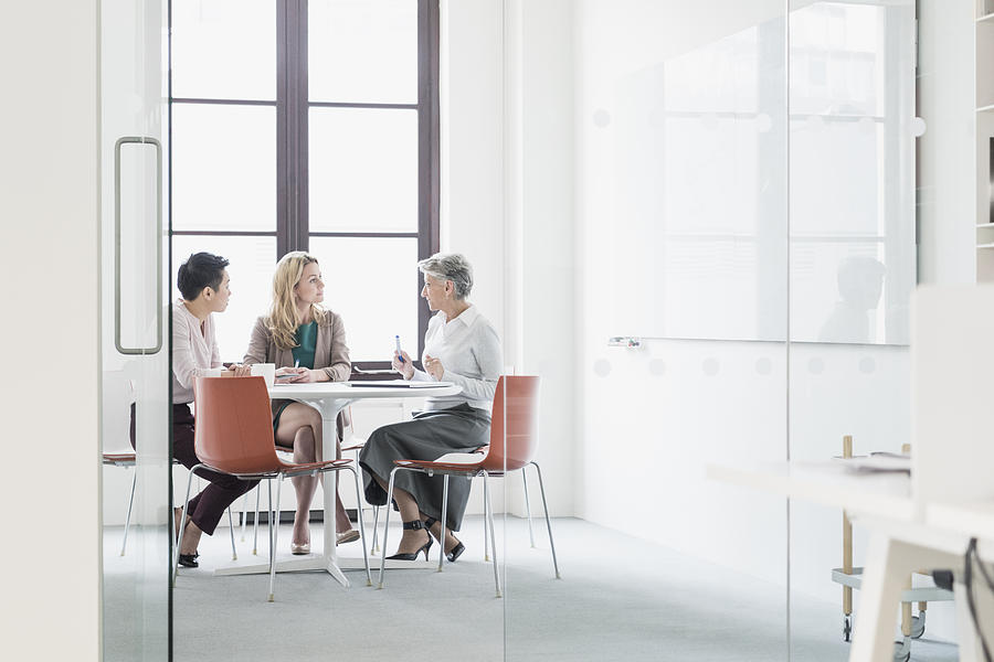 Three women sitting at table in modern office Photograph by JohnnyGreig