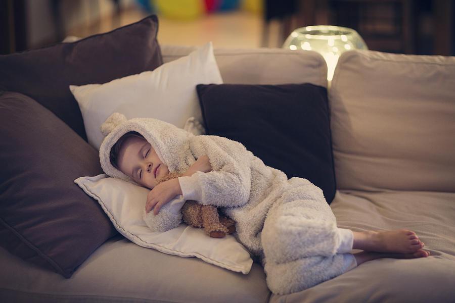 Tired child asleep on a sofa with teddy bear Photograph by Elva Etienne